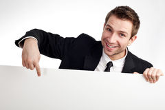 Businessman pointing at billboard. Portrait of young businessman pointing at blank white sign Stock Photography