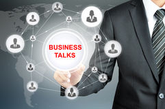 Businessman pointing on BUSINESS TALKS sign on virtual screen Stock Image