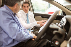 Businessman pointing a car interior Royalty Free Stock Photos