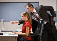 Businessman pointing at co-workers computer Stock Image