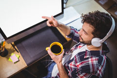 Businessman pointing at computer monitor while drinking coffee Stock Photography