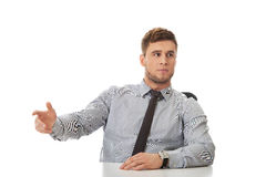 Businessman pointing by a desk in the office. Royalty Free Stock Image