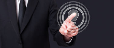Businessman pointing a digital idea bulb on virtual touchscreen Royalty Free Stock Image