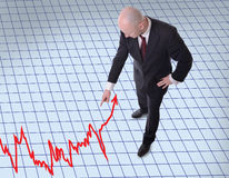 Businessman pointing down to graph. Businessman pointing downwards to a graph Stock Photography