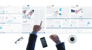 Businessman pointing at financial reports and news slides Royalty Free Stock Images
