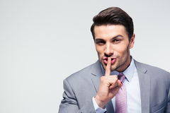 Businessman pointing finger over lips, asking for silence Royalty Free Stock Image