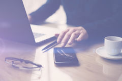 Businessman pointing finger on smartphone screen.Elegant coworker working at sunny office on laptop.Blurred background. Horizontal royalty free stock photography