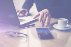 Businessman pointing finger on smartphone screen.Elegant coworker working at sunny office on laptop at the wooden table. Blurred background.Horizontal royalty free stock photography