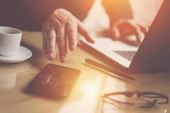 Businessman pointing finger on smartphone screen.Elegant coworker working at sunny office on laptop at the wooden table. Blurred background.Sunlight effects royalty free stock photo
