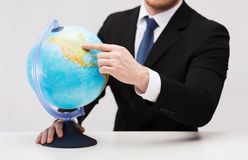 Businessman pointing finger to earth globe Stock Photos