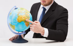 Businessman pointing finger to earth globe Royalty Free Stock Photos
