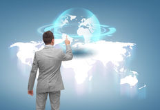 Businessman pointing finger to globe projection Stock Photos