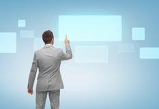 Businessman pointing finger to virtual screen Stock Photos