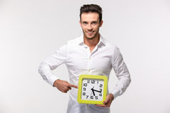 Businessman pointing finger on wall clock Stock Photo