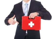 Businessman pointing at first aid box Stock Photo
