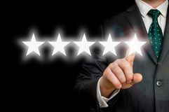 Businessman is pointing five stars - review and rating concept. Successful businessman is pointing five stars - review and rating concept stock photos