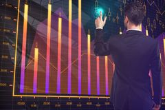 Businessman pointing at forex chart. Back view of young businessman pointing at forex chart. Stock and finance concept. 3D Rendering Royalty Free Stock Photo