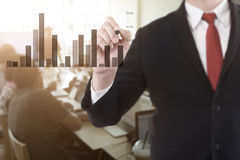 Businessman pointing a graph in conference room for a talking. Businessman pointing a graph in conference room for a talk business plan Royalty Free Stock Image