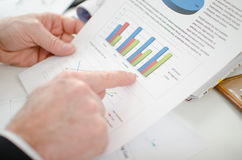 Businessman pointing a graph with his index finger Stock Photos