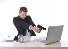 Businessman pointing gun to computer in overwork and overtime work concept. Young attractive European businessman working in stress at office desk computer Royalty Free Stock Photography