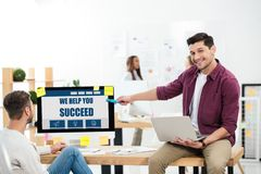 businessman pointing at we help you succeed inscription on computer screen while working at workplace with colleague stock photos