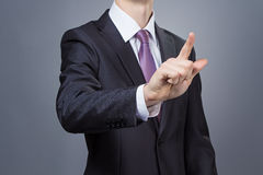 Businessman pointing his finger. Photo with grey background Royalty Free Stock Photos