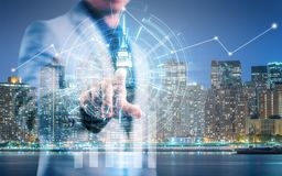 Businessman pointing his finger and touch the high technology screen with info-graphic. And night cityscape background Royalty Free Stock Image