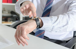 Businessman pointing his watch with his finger Stock Images
