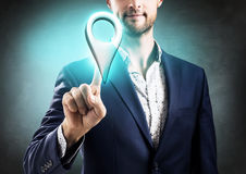 Businessman pointing on indicating location icon. Over gray wall background Royalty Free Stock Photos
