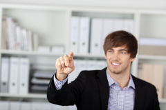 Businessman Pointing At Invisible Screen In Office Royalty Free Stock Images