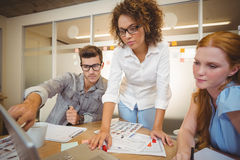 Businessman pointing on laptop as female colleagues looking at it Royalty Free Stock Photos