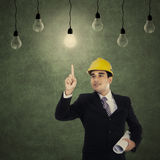 Businessman pointing at light bulb Royalty Free Stock Images
