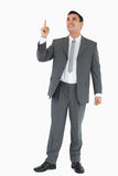 Businessman pointing and looking upwards Stock Image