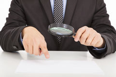 Businessman pointing through a magnifying glass Royalty Free Stock Images