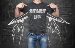A businessman is pointing out in the chest where is a word collocation ' start up '. A concept of the starting up new business. Stock Photo