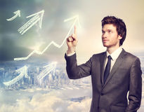 Businessman pointing rising arrows Royalty Free Stock Photography