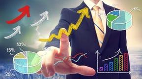 Businessman pointing at rising arrows Royalty Free Stock Photos