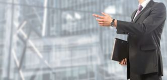 Businessman pointing at screen on blurred and spacious background stock images