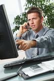 Businessman pointing at screen at desk. Troubled businessman pointing at screen disussing work on mobile phone sitting at office desk Royalty Free Stock Photos