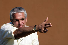 Businessman pointing/shooting. Portrait of businessman pointing/shooting on brown background Stock Photos
