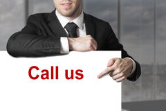 Businessman pointing on sign call us. Businessman in office room pointing on sign call us Stock Images