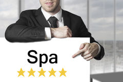 Businessman pointing on sign spa golden stars. Businessman in black suit poitning on sign spa golden rating stars royalty free stock photography