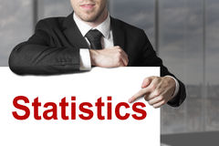 Businessman pointing on sign statistics Stock Photo