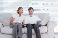 Businessman pointing something on laptop to her colleague Stock Photography