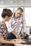 Businessman Pointing At Something To Coworker. Businessman sitting on desk pointing out at something to coworker Royalty Free Stock Photos