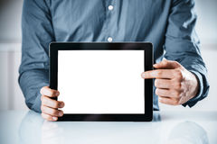 Businessman pointing to a blank tablet-pc. Close up of the hands of a businessman pointing to the blank screen of a tablet-pc drawing your attention to copyspace royalty free stock images