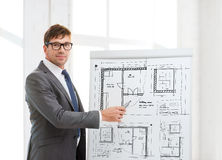 Businessman pointing to blueprint on flip board stock images