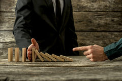 Businessman pointing to falling dominos and his partner stopping. Them in a conceptual image of cooperation and mentor Stock Photo