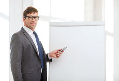 Businessman pointing to flip board in office Royalty Free Stock Photo