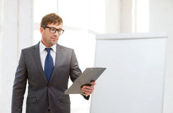 Businessman pointing to flip board in office Royalty Free Stock Photos